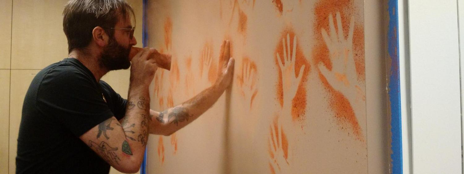 Man painting hand figures on a wall.