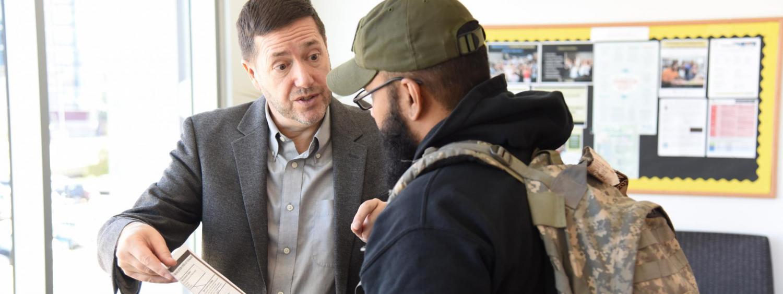 photo of Stephen Hartnett talking to a student