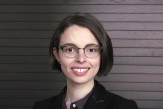 A white woman with short brown hair and glasses.