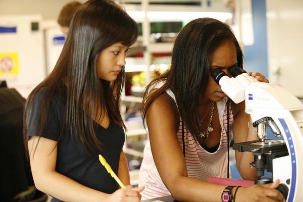 2 girls looking in microscope