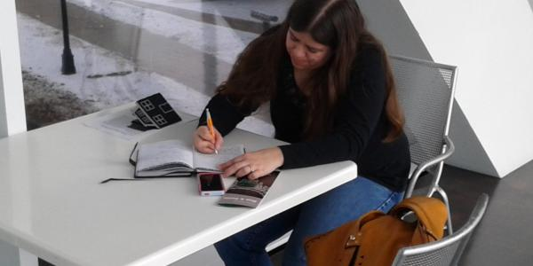 A woman writing on a notepad at a table