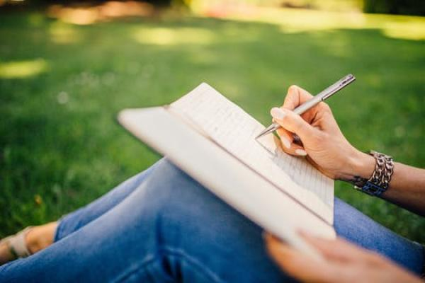 Hand holding pen writing in journal resting on knees