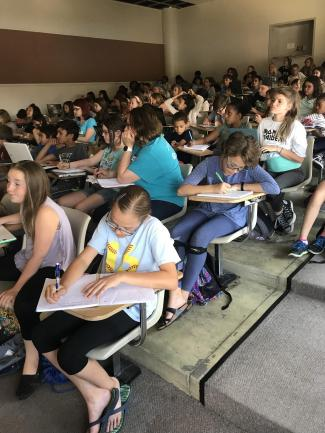 Cherry Creek campers writing at desks