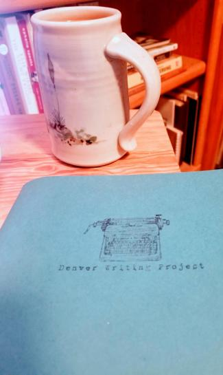 mug with coffee on table with notebook that says Denver Writing Project
