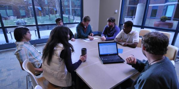 Students gathered around a table looking at a laptop computer