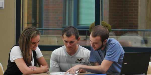 Three students looking over a document
