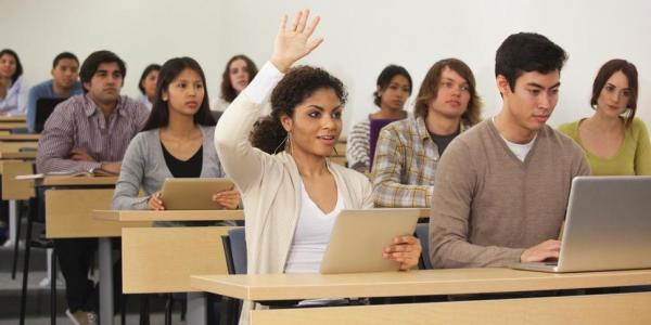 Students in classroom, woman raising her hand