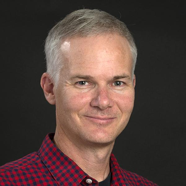 Man with short grey hair wearing a red and blue checkered collared shirt