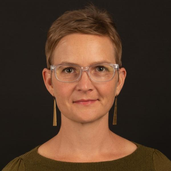Woman with short brown hair and clearn glasses with long, triangular dangly earrings against a black background