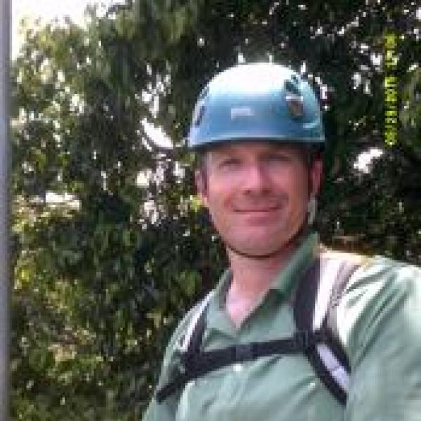 Man wearing climbing helmet with a backpack on
