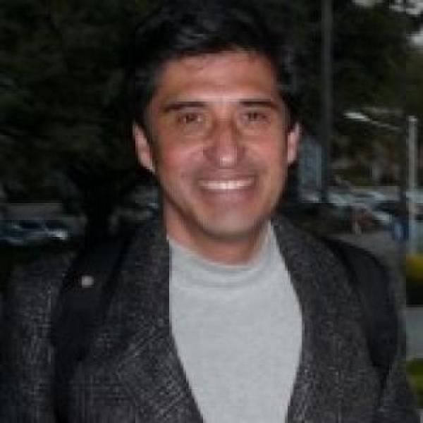 Man with short dark hair smiling wearing backpack and a grey blazer