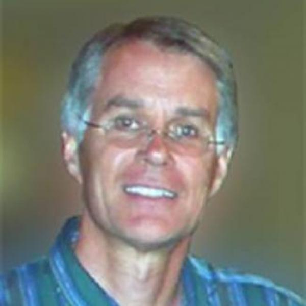 Headshot of grey-haired man smiling wearing glasses