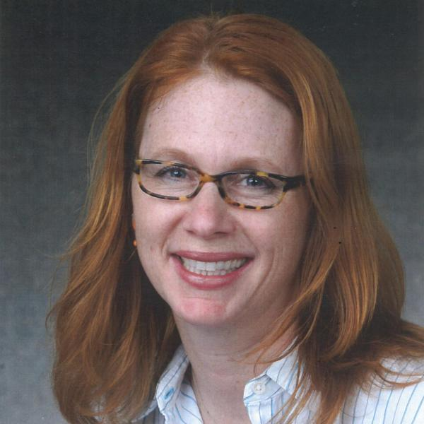 Headshot of red-haired woman wearing glasses