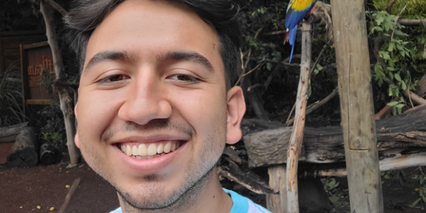 Headshot of man smiling with dark short hair, small amount of facial hair, with a red, orange, and blue parrot in the background
