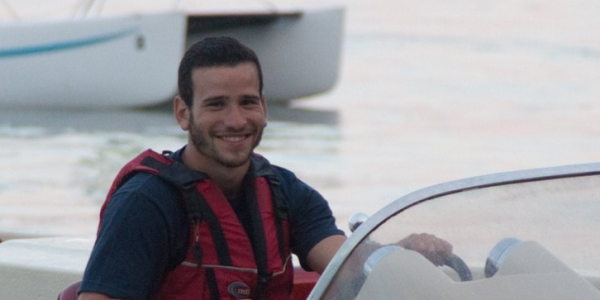 Man with short black hair smiling driving a boat in a blue shirt and a red lifejacket