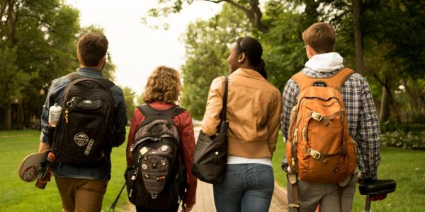 Four students walking down the sidewalk