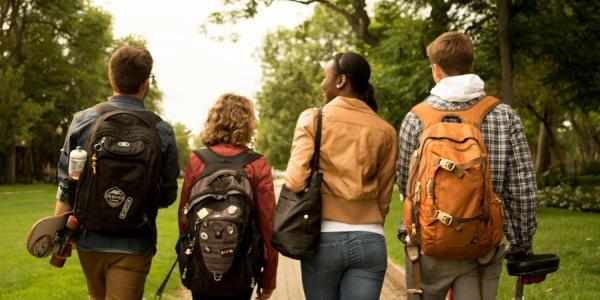 Four students walking down a sidewalk