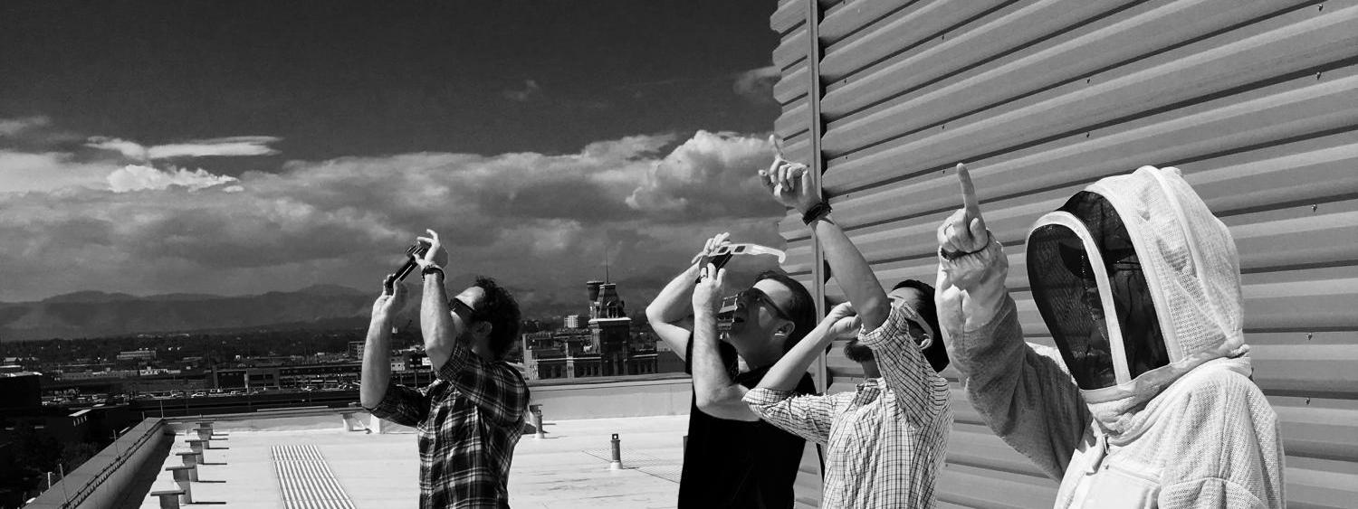 Faculty observing the 2017 Solar Eclipse on a rooftop