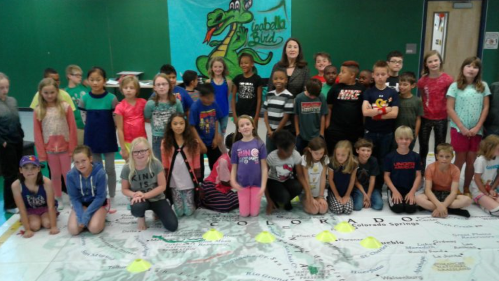 Young students posing for a photo on a giant map of Colorado