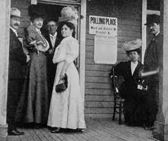 women standing in the doorway of a polling station