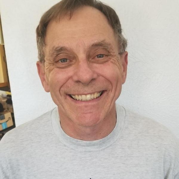 Jose Carbon wearing a gray tshirt smiling.
