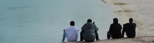 Photo of migrant men sitting on beach