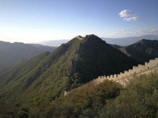Picture of the Great Wall of China surrounded by green trees.