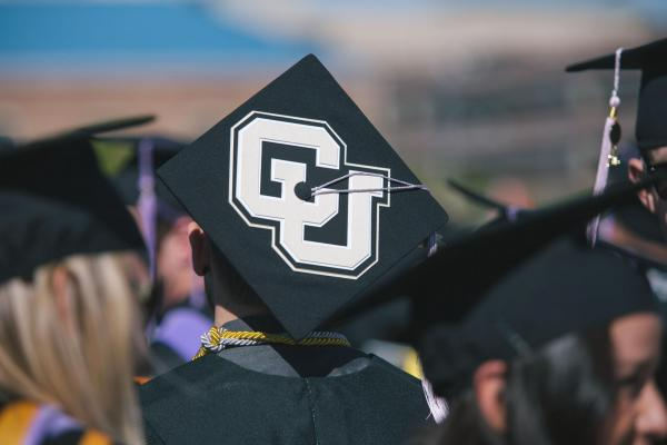 a person wearing a graduation cap with the CU logo on it