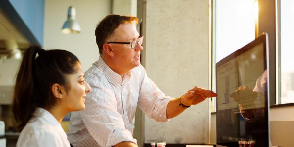 A professor showing a student something on a computer screen