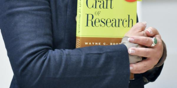 Photo of person holding a research textbook.