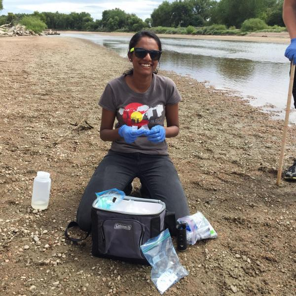 Researcher with sampling supplies by the waterside