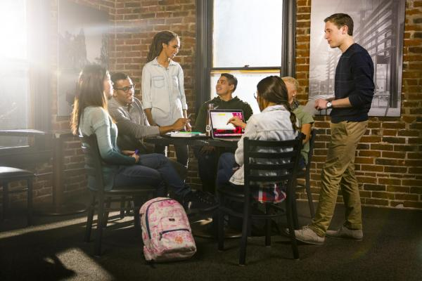 Students talking near brick wall