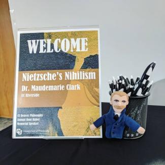 Poster for Nietzsche's Nihilism lecture and Nietzsche plush