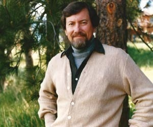 Dr. John G. Weihaupt standing in front of a tree