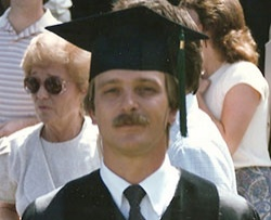 Dr. Anthony Piccone standing in a graduation cap
