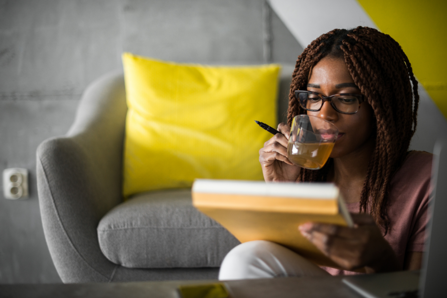 A woman sits in front of a grey seat sipping tea while contemplating her writing on the notebook in front of her.