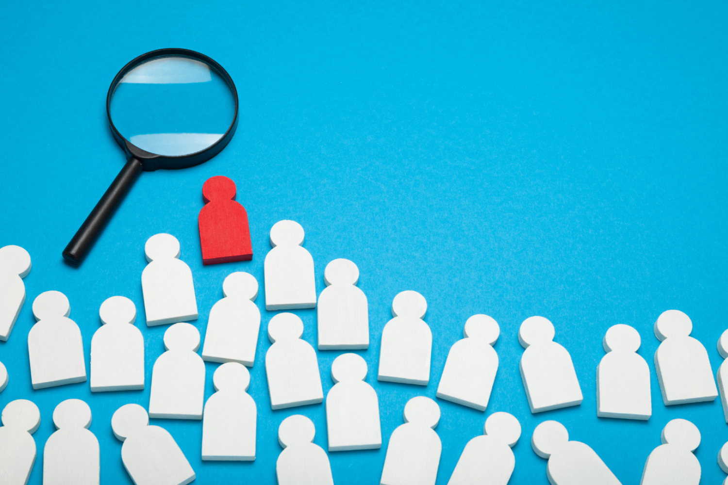 A magnifying glass hovers over a blue background with white icons of people. One of the icons is highlighted red to indicate the person was chosen.