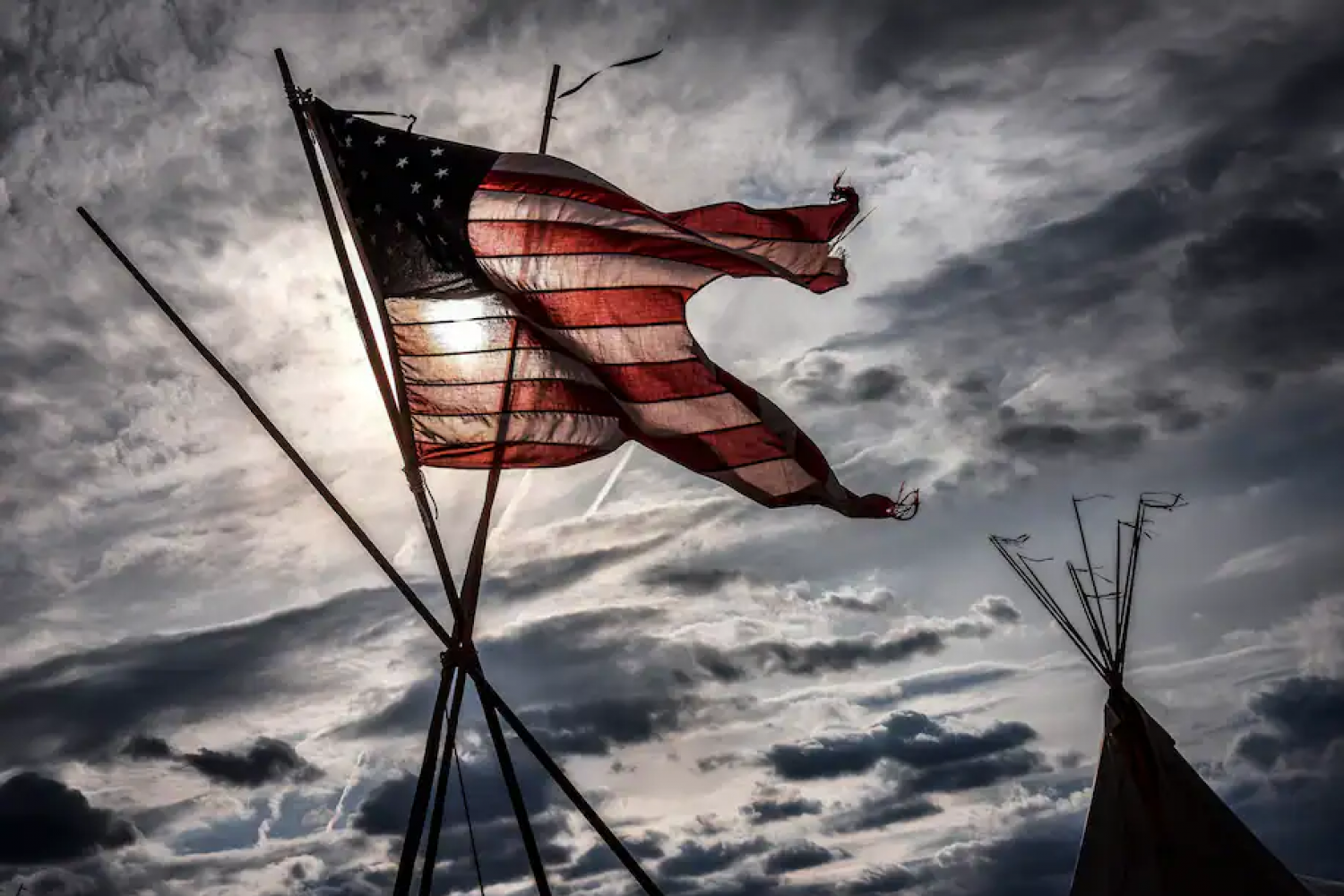 A U.S. flag is flown over a Native American tepee erected during a protest in Washington in 2017. (Bill O'Leary/The Washington Post)