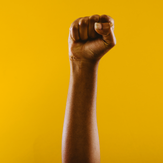 A protest fist raised to the sky with yellow background