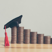 Photo of coins stacked on counter with graduation cap on top to indicate scholarship availability