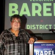 "Veronica Barela stands next to podium reading ""City Council Veronica Barela District 3"" Photo by Joe Contreras"