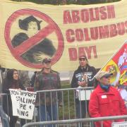 Protestors stand with signs reading Abolish Columbus Day