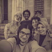 A group of students and faculty member take a smiling selfie in front of a building with two columns.