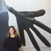 Tania Islas Weinstein in front of an artpiece displaying a large hand in black and white.
