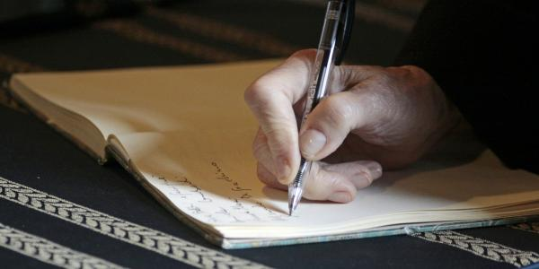 Image of a hand holding a pen and writing in a notebook