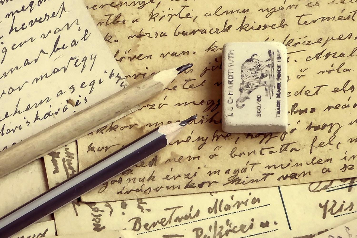 image of pencils, an eraser, and paper with cursive writing on it.
